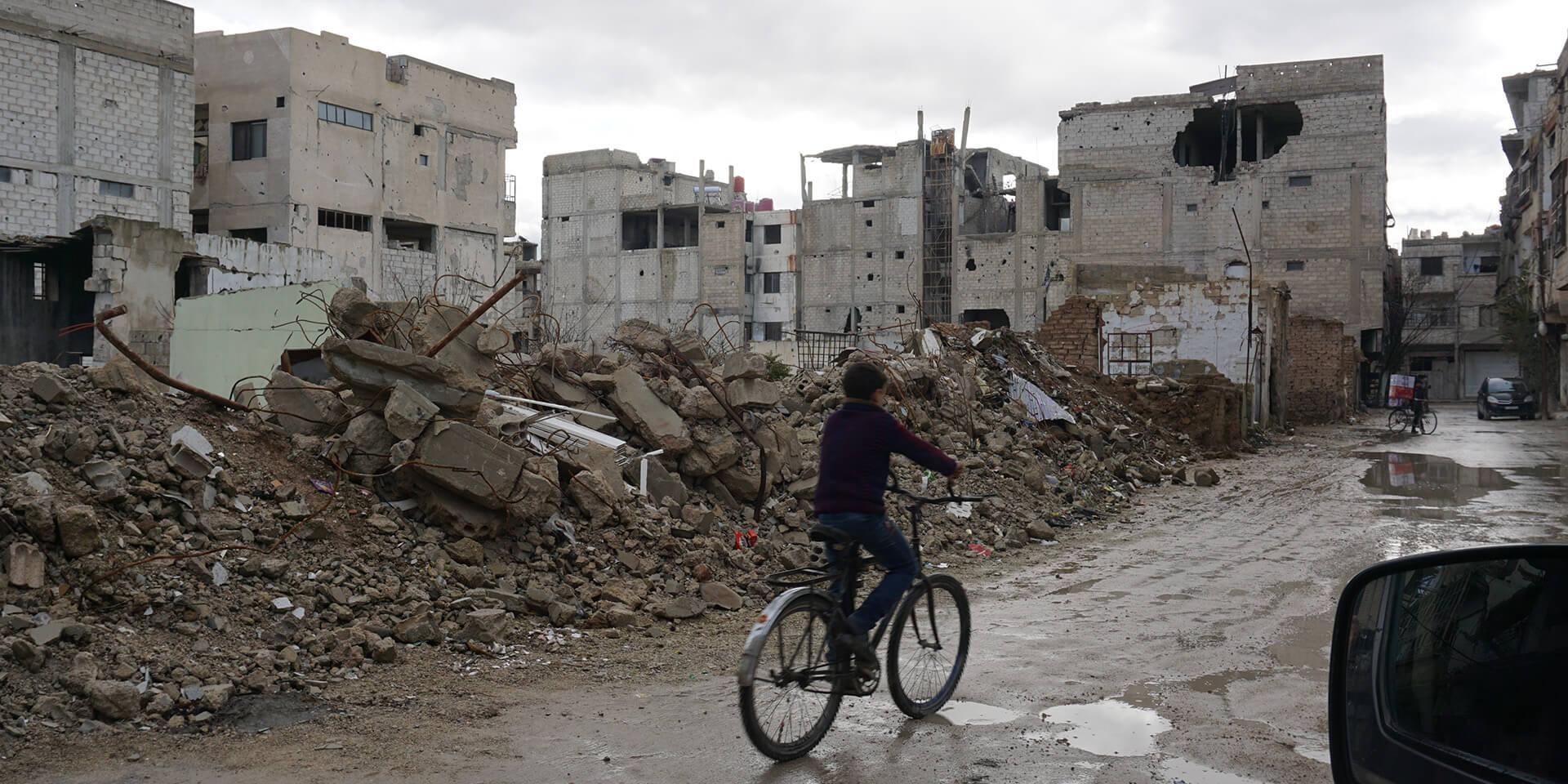 Mit dem Fahrrad durch die zerstörten Häuser in Irbin.